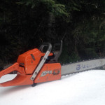 A chainsaw sitting on a snowbank with trees in the back