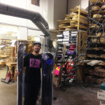Matt holding a pair of NEH skis and a NEH snowboard on the factory floor