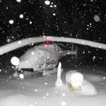 A helicopter on the hei pad covered with snow and lots of snow falling from the sky during the record snowfall in Terrace