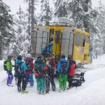 A group of skiers and snowboarders loading into a snowcat at the bottom of a run. It is snowing.
