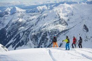 Heli ski group standing on a mountain ridge ready to ski powder.