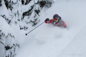 Ryan Merrill skiing deep snow in the trees at Northern Escape Heliskiing.