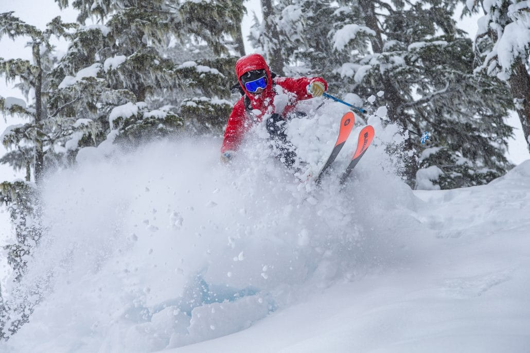Heli skier catching air in the powder on some Blizzard Rustler 11 skis.