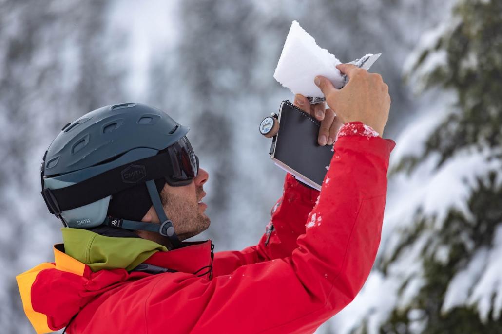 heli ski guide taking snow measurement